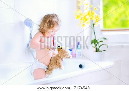 Baby Girl Brushing Teeth Playing With A  Bear