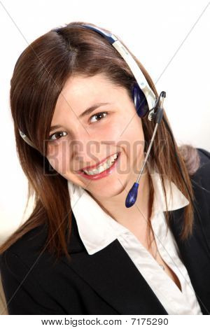Young Woman In A Call Center. She Wears A Headset Smiles Toward The Camera