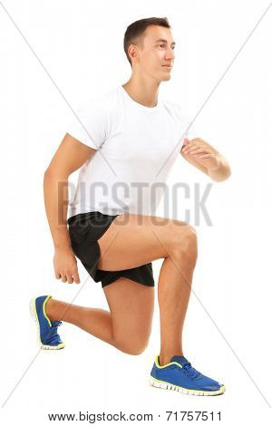 Handsome young sportsman execute exercise isolated on white