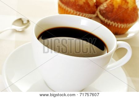 a cup of coffee and a plate with some magdalenas, typical spanish plain muffins, on a set table