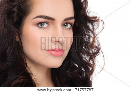 Close-up portrait of young beautiful woman with fresh clean make-up and curly hair over white background