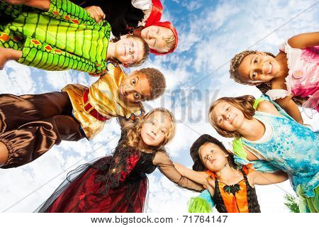 Many kids, Halloween costumes look down in circle