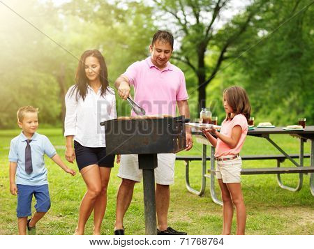 dad grilling food for wife and kids at outdoor cookout