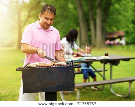 father grilling hot dogs and bratwurst for family at barbecue