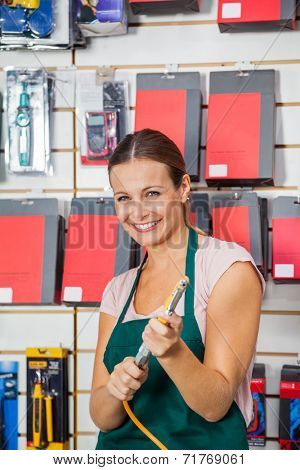 Portrait of happy mid adult saleswoman holding air compressor hose in hardware store