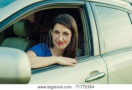young beautiful successful woman driving an expensive car
