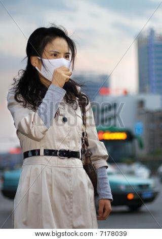 Mujer asiática con una máscara de la cara