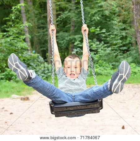Hilarious boy have a fun on a garden swing.