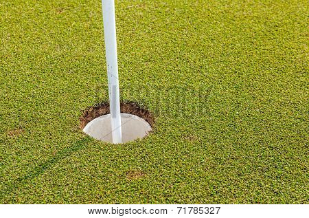 Golf Hole And Flag On Green Grass Of Golf Course