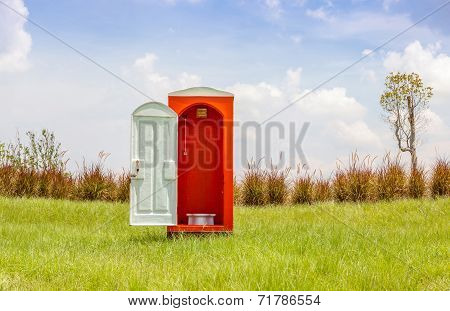 The Red Toilet With White Door Open Contrast With Green Grass And Tree In The Meadow.