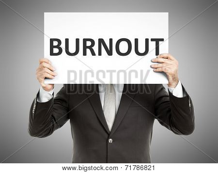 A business man holding a paper in front of his face with the text burnout