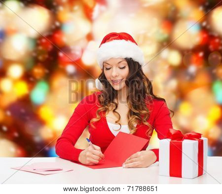 christmas, holidays, celebration, greeting and people concept - smiling woman in santa helper hat with gift box writing letter or sending post card over red lights background