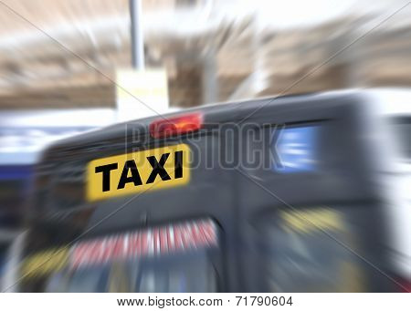 Taxi waiting at railway station. Zoom effect added which is focused on sign.