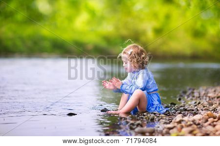 Little Girl Playing At River Shore