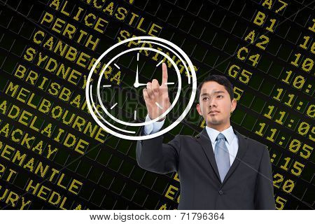 Serious asian businessman pointing to a white clock against black airport departures board for australia