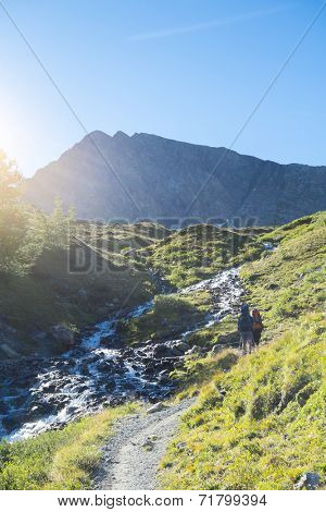 COMBAL, ITALY - AUGUST 28: Hikers walking up path by creek with Charmonts Peaks in the background. The area is on a stage of the popular European Mont Blanc tour. August 28, 2014 in Combal.