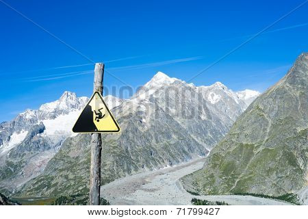 COMBAL, ITALY, AUGUST 28: Slippage danger sign with Miage Glacier and Combal peaks in the background. The area is on a stage of the popular European Mont Blanc tour. August 28, 2014 in Combal.