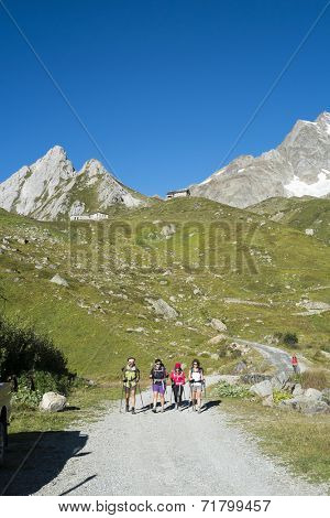 VAL VENY, ITALY - AUGUST 28: Hikers walking on dirt road with Elisabetta Soldini Refuge in the background. The refuge is on a stage of the popular Mont Blanc tour. August 28, 2014 in Val Veny.