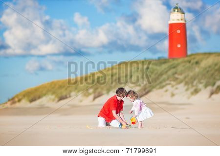 Brother And Sister Playing On The Beach Next To A Lighthouse