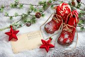 image of new years baby  - vintage christmas decoration red stars sweets and antique baby shoes over snow background - JPG