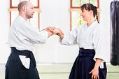 foto of aikido  - Man and woman fighting at Aikido training in martial arts school  - JPG