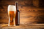 stock photo of ear  - Glass and bottle of beer with wheat ears on wooden planks - JPG