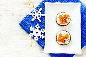 stock photo of canapes  - canape with salmon and cream cheese with dill for Christmas on a light woody background - JPG