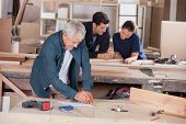 stock photo of coworkers  - Senior architect working on blueprint with coworkers in background at workshop - JPG