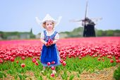 stock photo of national costume  - Adorable curly toddler girl wearing Dutch traditional national costume dress and hat playing in a field of blooming tulips next to a windmill in Amsterdam region Holland Netherlands - JPG