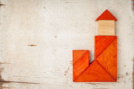 stock photo of tangram  - abstract house with a tower or church built from seven tangram wooden pieces - JPG