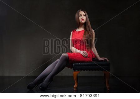 beautiful model sitting on chair in studio