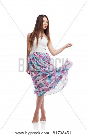 Young woman posing in long dress isolated on white