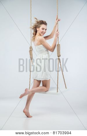 Young bare-footed girl by swing looking in camera