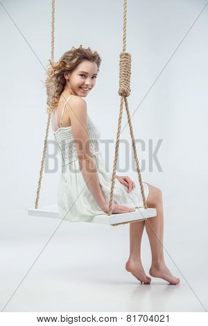 Beautiful smiling woman sitting on swing isolated