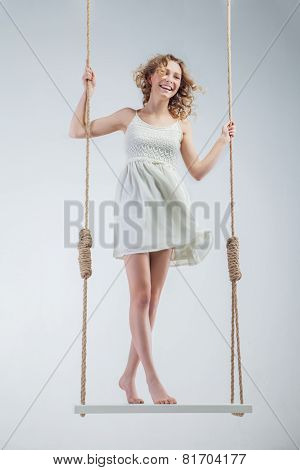 Young loughing bare-footed girl on swing