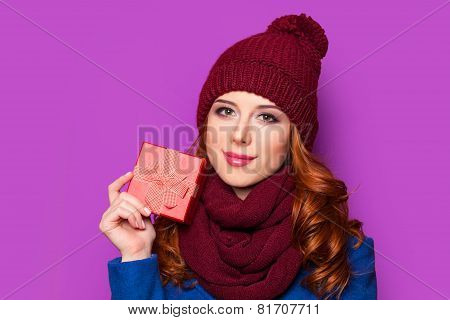 Beautiful Redhead Girl With Christmas Gift On Violet Background.