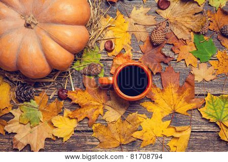Pumpkin, Leafs, Chestnuts With Cone And Cup Of Coffee On A Wooden Table.