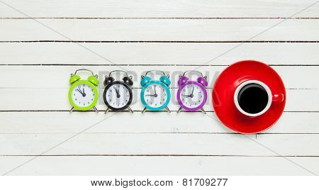 Four Alarm Clocks And Cup Of Coffee
