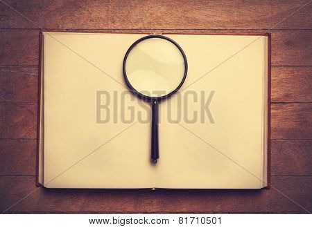 Opened Book And Loupe On It.