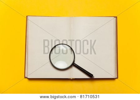 Opened Book And Loupe On Color Background.