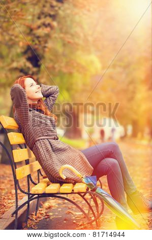 Style Redhead Girl Sitting At Bench In Autumn Park.