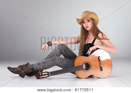 The beautiful girl in a cowboy's hat and acoustic guitar.