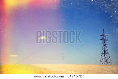 Electrical Net Of Poles On A Panorama Of Blue Sky And Wheat Field