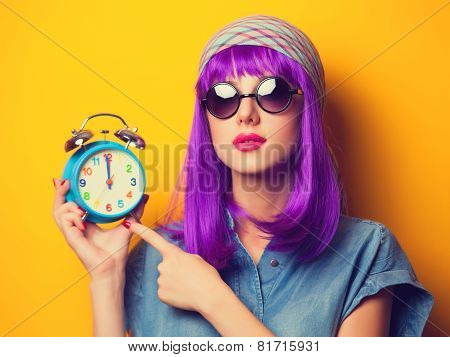 Beautiful Girl With Violet Hair In Sunglasses And Alarm Clock On Yellow Background.