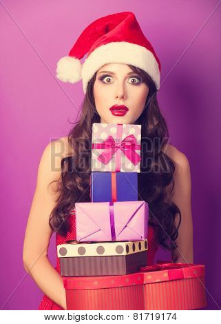 Beautiful Brunette Girl In Christmas Hat With Gifts  On Violet Background.