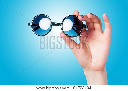 Hand holding sunglasses on blue background