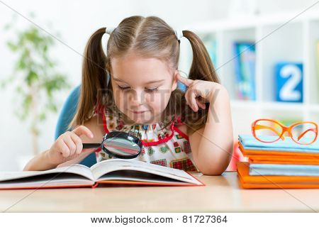 cute kid looking through a magnifying glass with book