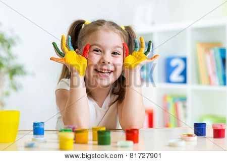 beautiful child girl with hands in color paints