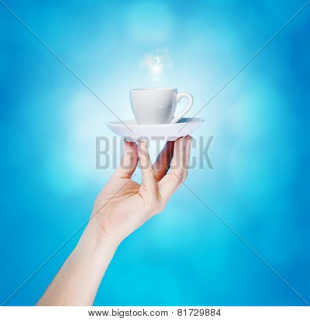 Hand Holding white Cup On Blue Background