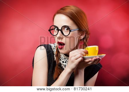 Redhead Girl With Cup Of Coffee On Red Background.